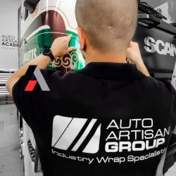 Car wrapping specialist putting vinyl foil or film on car.